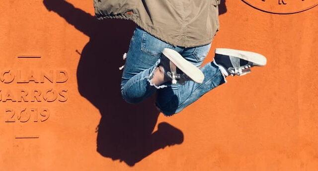 オレンジの壁の前で軽快にジャンプする女性の足元