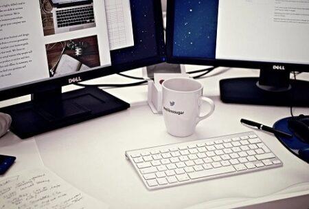 デュアルPCで作業中の、マグカップの置かれたテーブルの上の風景