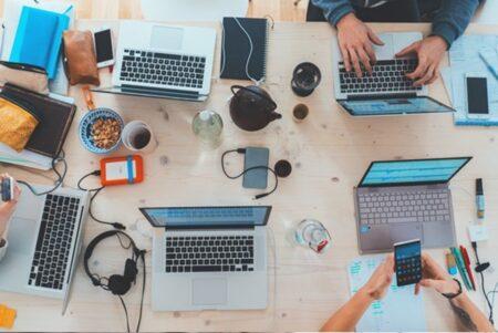 人_複数のパソコンとデバイスを使って作業をしている人々