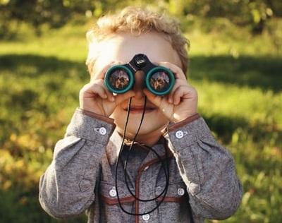 人_緑の縁取りの双眼鏡をつかって、こちらを微笑みながらのぞき込む小さな男の子