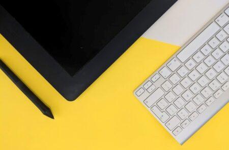 黄色いテーブルに置かれた白いキーボードと板タブレット