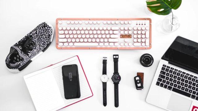 パソコンとノートと靴と時計の置かれた風景
